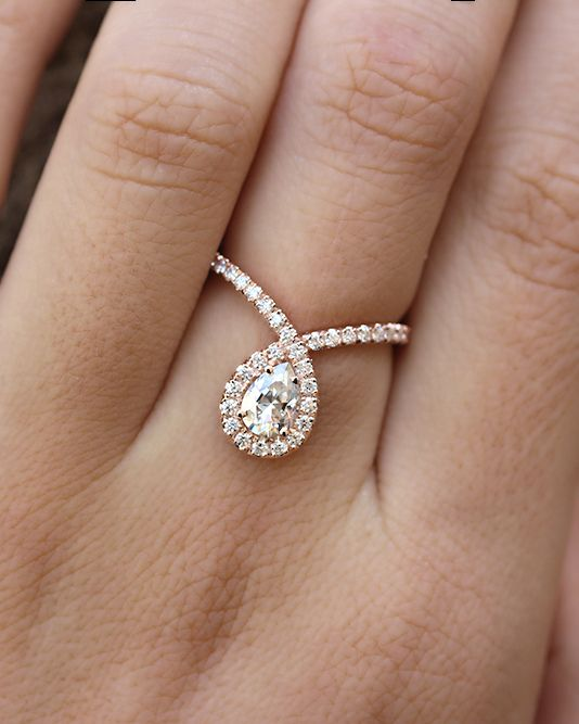 Pear shaped Moissanite engagement ring with pave diamonds in 14K white gold.