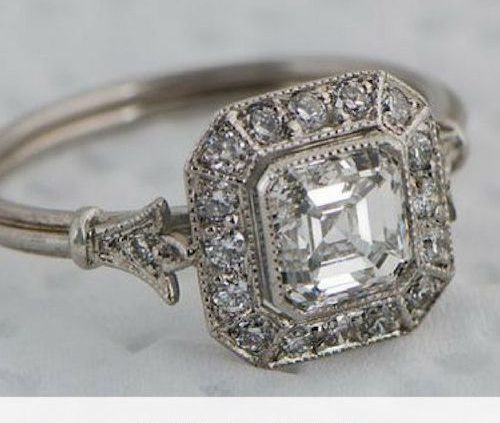 Beautiful vintage style Asscher diamond ring. It is surrounded by sixteen brilliant diamonds. A fleur-de-lis design and triple wire shank add to the delicacy of this ring. The ring has a GIA certification.