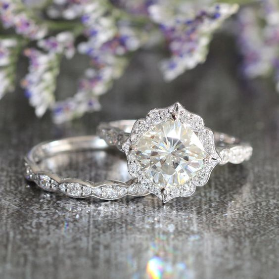This bridal wedding ring set showcases a floral engagement ring with a cushion cut set in a solid white gold scalloped diamond band.