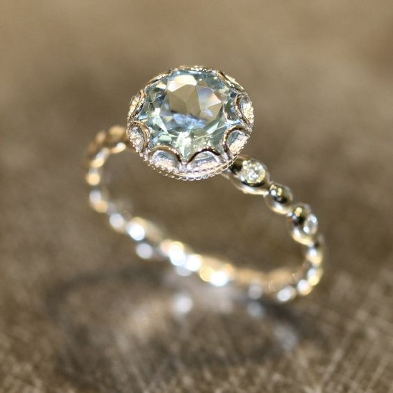Stunning feminine and romantic! This aquamarine ring is crafted in white gold with a round shaped aquamarine set into a gorgeous floral basket setting on top of a diamond pebble band. Breathtakingly elegant and beautiful.