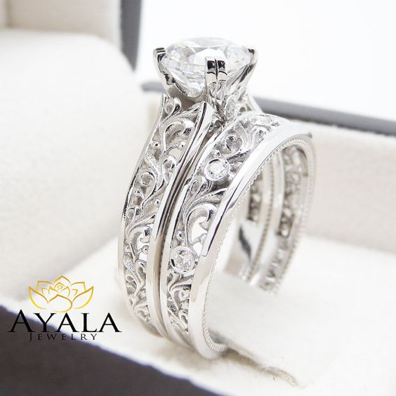 A unique diamond sits atop in breathtaking detail. This art deco bridal ring set also includes a diamond encrusted wedding band that fits within the design for a seamless look when worn.