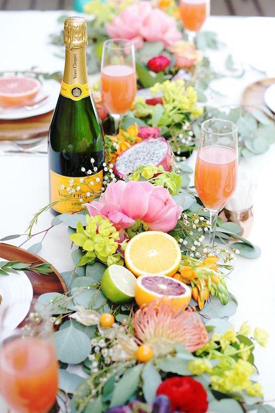 Un centro de mesa cítrico sobre hojas con flores y gipsófilas entremezcladas formando una guirnalda.