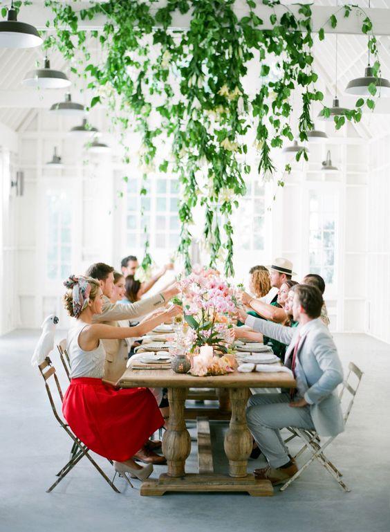 La simpleza de la decoración inspirada en Cuba en un salón con mesas de madera, centros con flores y mucho verde colgando del techo. Fotografía: Jose Villa Photography.