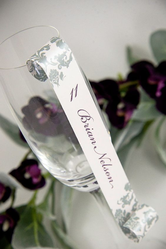 Show your guests their assigned table with these impressive seating card scrolls! Damask pattern double-sided champagne flute seating card scroll in plum, sage, and nude.