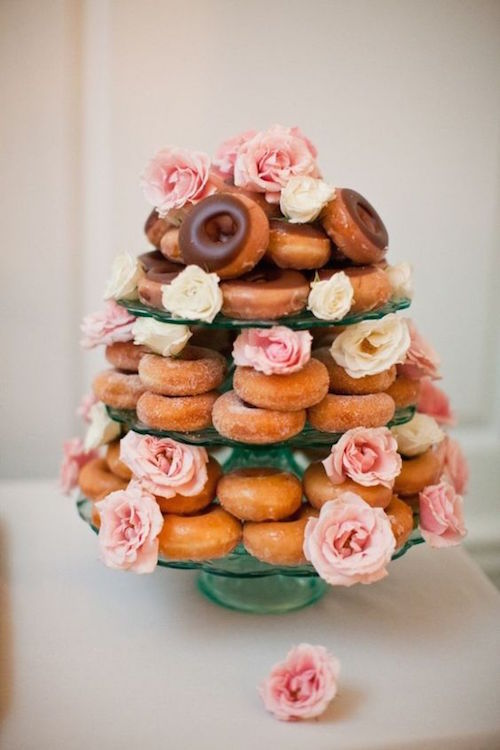 A three tiered glass cake stand combined with a garnish of white and pink roses transform this plain doughnuts stack into something spectacular. Photo: MegRuth Photo.