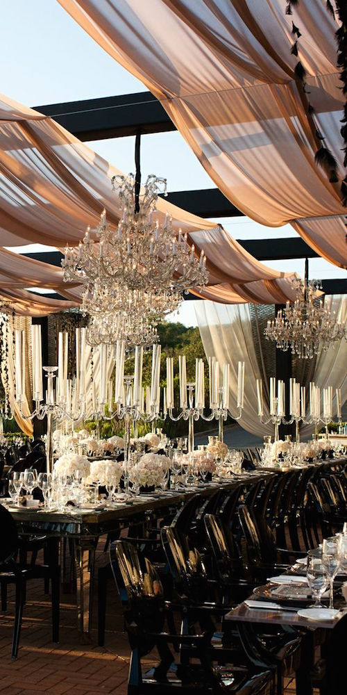 Candelabras with tall tapered candles and hanging chandeliers for an upscale outdoor wedding.