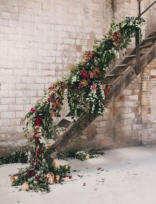 Floral garland and candle lanterns down the stairs of a modern industrial fall wedding. Photo: Albert Bardina Photography.