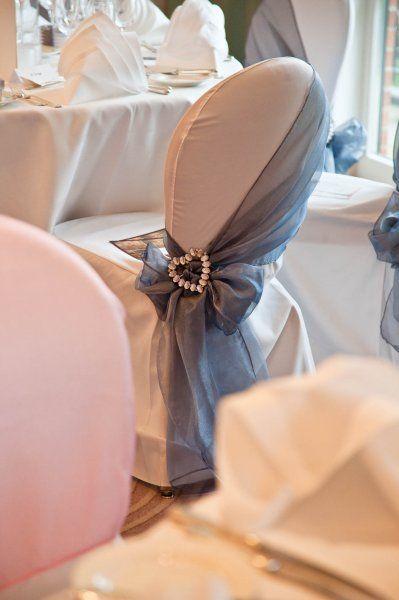 Una manera muy chic y elegante para envolver y decorar sillas de boda. Un drapeado hacia el costado en tela de tul atado con un corazón de strass.