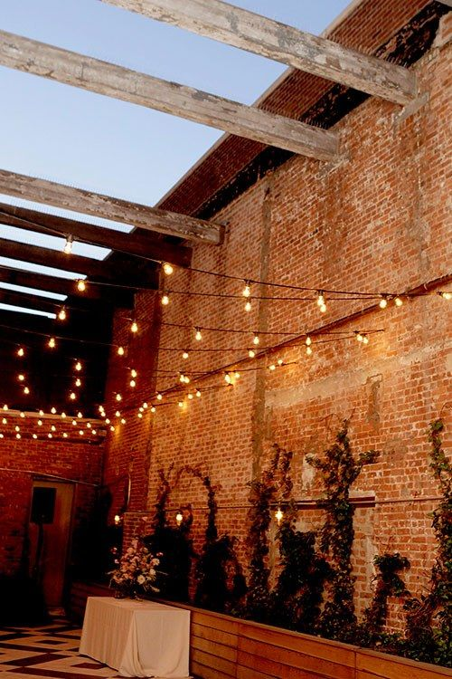 A garden-inspired industrial wedding in New York at The Wythe's patio, complete with exposed beams and strings of café lights.