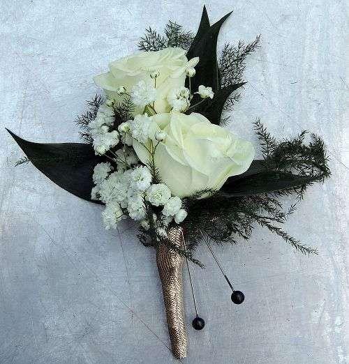 Boutonniere con dos rosas envuelto con cinta de vástago de cinta y follaje.