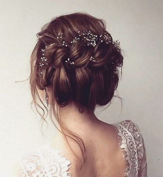 The braided up-dos trend shines on this messy twisted wedding hairstyle with dainty hair accessories.
