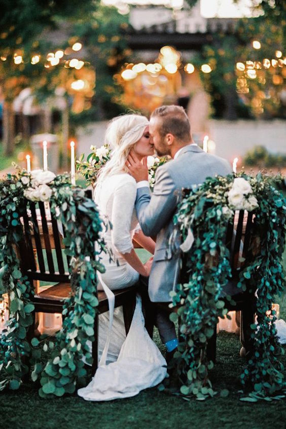 Love the greenery decorating the bride and groom chairs and the tapered candles on the table. So glam! Arizona Wedding Photographer: Megan Robinson.