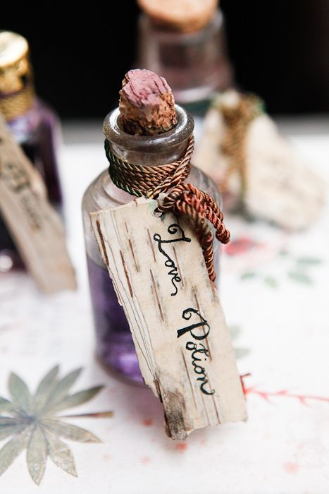 Love potion bottles filled with grape juice. A perfect addition to an enchanted forest wedding theme.