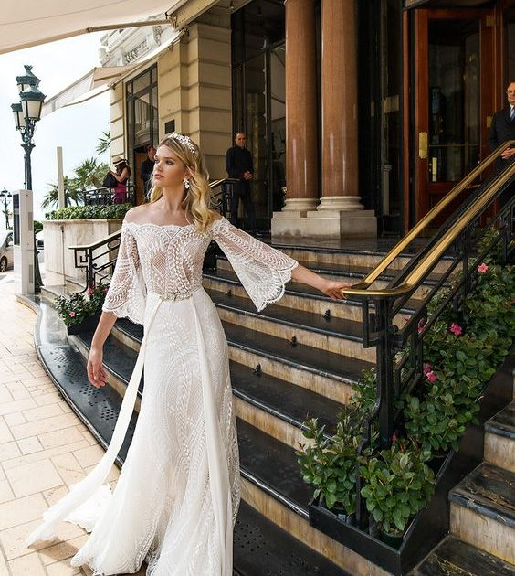 For the hipster bride, the alessandra rinaudo 2017 bridal brings you Bria - with off the shoulder three quarter bell sleeves lace heavily embellished bodice sexy sheath wedding dress lace back and a sweep train.