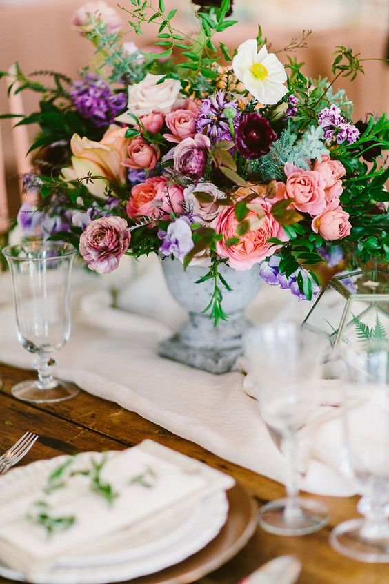 Plum and coral flowers to show you that there is no need to stick to earthy tones when planning an enchanted forest wedding. One Space photography by Redfield Photography.