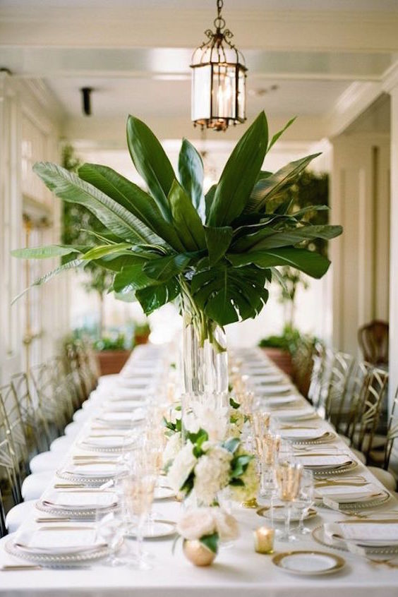 A wedding tablescape with gold tones in flatware, guest chairs, and place settings. A wedding Inspired by Ernest Hemingway.