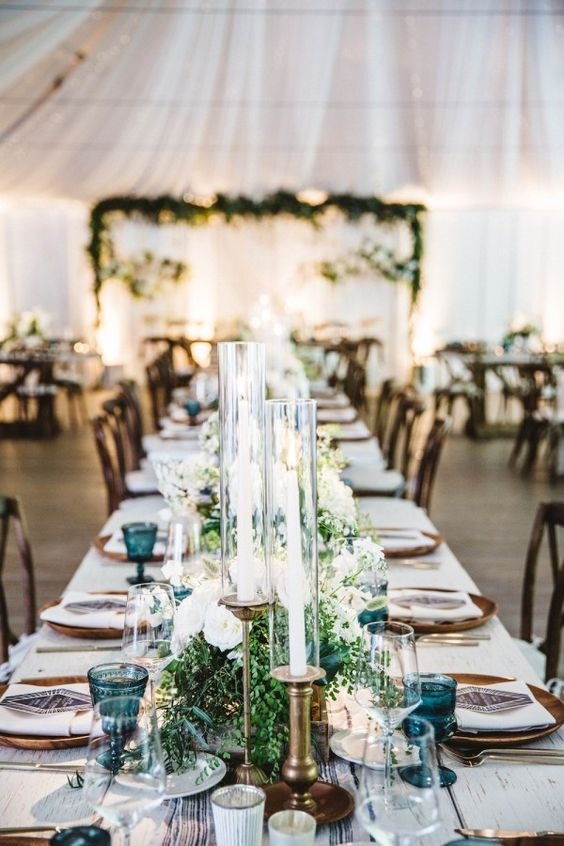 Boho chic wedding at Calamigos Ranch. Tables cape on a white wood table, blue goblets, and candles. Outstanding wedding decor.