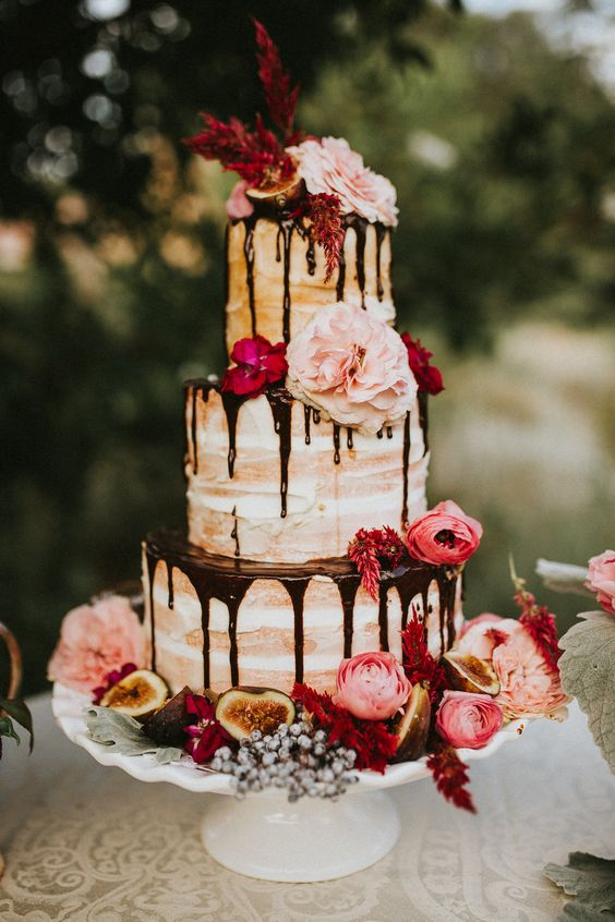 Drip cakes are the latest trend in weddings. Check out this flower topped naked wedding cake with chocolate drizzle.