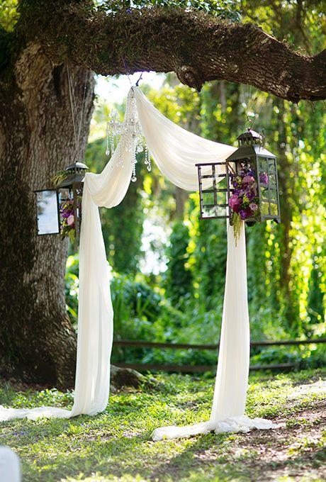 Lo rústico se torna único con este arco de bodas cubierto con tela, con linternas llenas de flores y un chandelier de cristal, todo dentro de las ramas de un árbol.