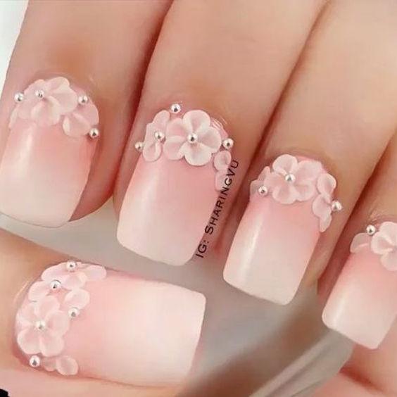 Decoración de uñas en ombré creada con esmalte rosa y blanco. Para que resalte aun más, se agregaron detalles al borde de las cutículas con flores bien pequeñas y se finalizó con perlitas en plateado sobre las flores.