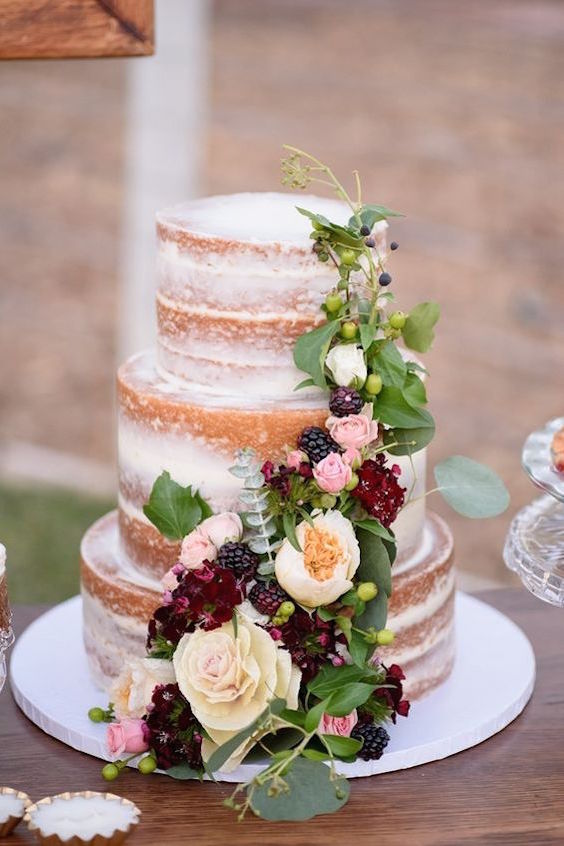 Garden wedding? Naked cake draped in flowers & berries. Pomegranates & berries, rustic glam. Wedding photographer: The Amburgeys.