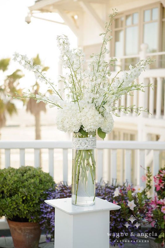 A vintage classic wedding by the beach in pink, blush, white, and peach. Some amazing pictures by Wayne & Angela .Tall white arrangements of hydrangea, dendrobium orchid and delphinium were placed on pedestals framing the bride and groom.