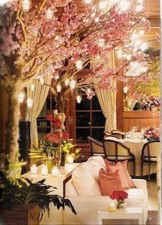 Fabulosa decoración con lounge para bodas. Un sofá, mesitas, almohadones y un árbol iluminado.