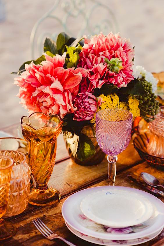Mix and match your tableware and add a pop of color with some flowers like these dahlias.