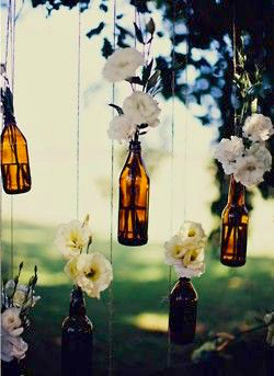 Hanging bottles and flowers for an outdoor Boho ceremony. Find out how to plan a boho wedding!