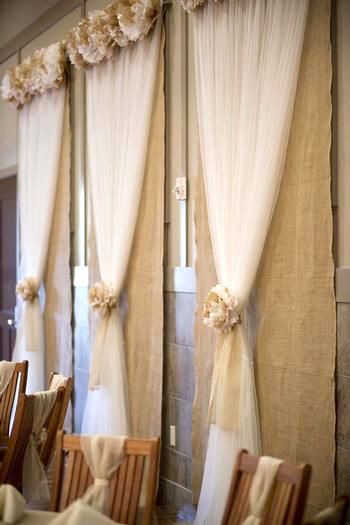 Burlap and tulle window covers with rosettes. Done with coral and ivory flowers. An easy and cheap idea to help cover windows if the reception space is too bright.