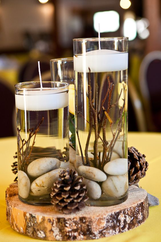 Rustic centerpieces with candles, rocks and pinecones.