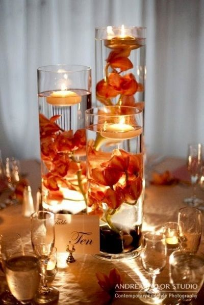 Tall cylindrical vases with water and floating bright red or orange flowers and tea candles. Discover how to make these stunning lighted centerpieces for wedding receptions.