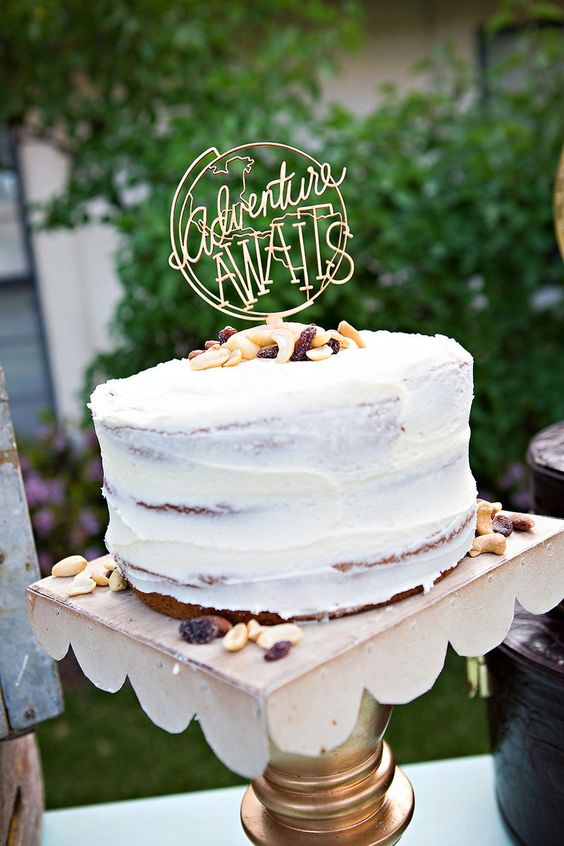 """Adventure awaits"" travel or wanderlust wedding cake topper. Notice the nuts surrounding the cake. So cool."
