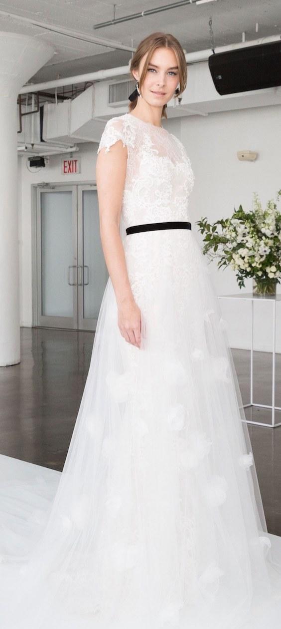 Este vestido con corte en línea A luce un top de encaje bordado estilo ilusión con mangas japonesas que envuelve la falda de tul. Para una novia romántica y moderna. Marchesa 2018.
