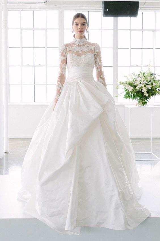 Luce como una princesa en este vestido de novia con mangas largas tipo ilusión, escote corazón, ceñido a la cintura con falda voluminosa en 3-D.