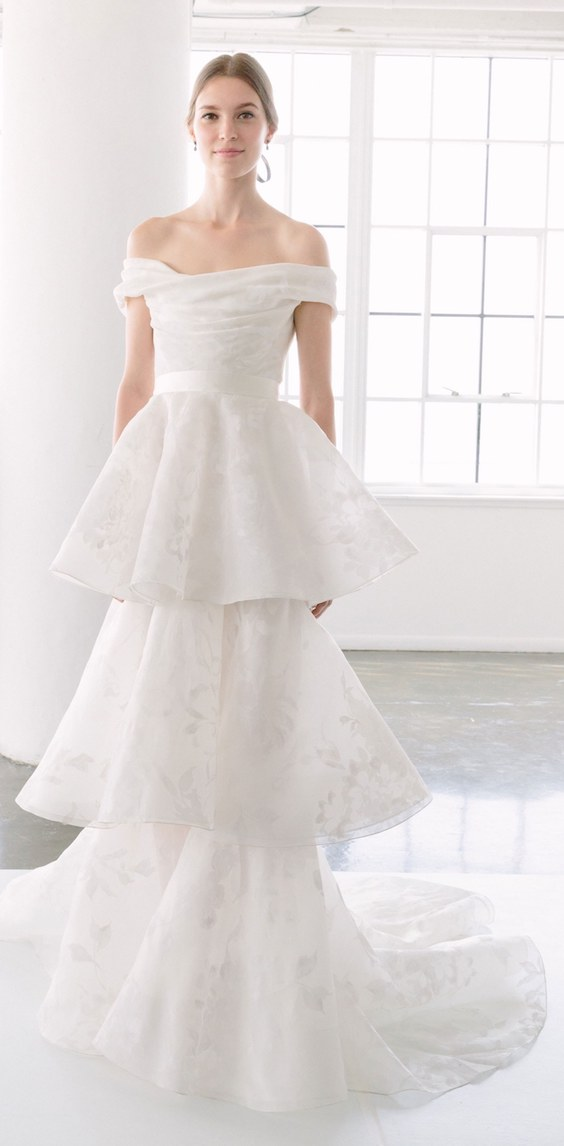Una interpretación moderna y romántica del vestido de novia tipo columna con un delicado escote palabra de honor con falda en capas de Marchesa.