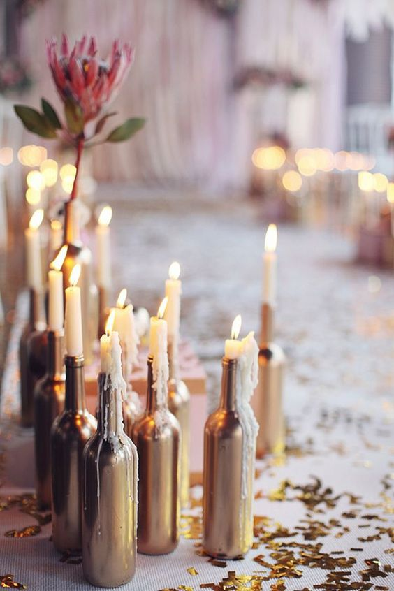 Vintage wedding centerpiece ideas. Painted gold bottles as candle holders.