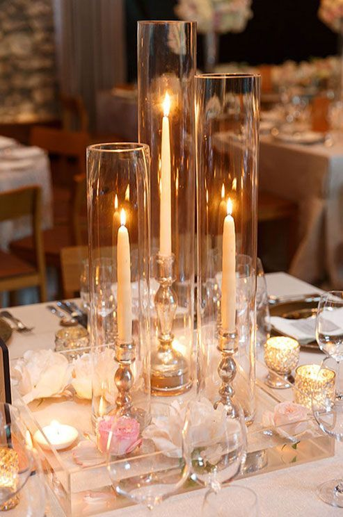 Alternating votive and taper candles is both beautiful and practical, allowing guests to interact across this simply chic reception table. The cylindrical vases will protect the candles from accidentally falling.