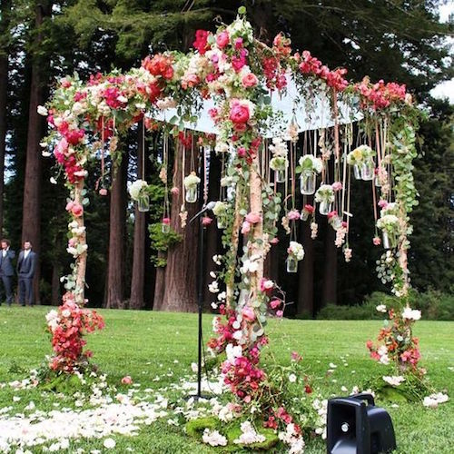 Romantic outdoor pink and red flower Boho wedding ceremony decor via Amy Burke Designs.