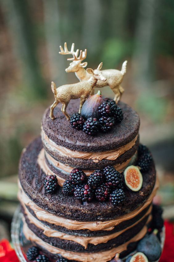 Dark woodland enchanted forest wedding inspiration in black, red, and gold with seasonal elements and animal cake toppers. Wedding photographer: Artemis Photography.