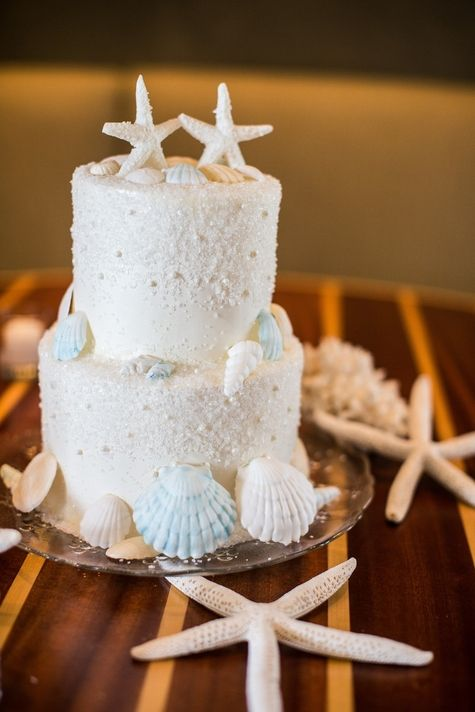 The shells, the starfish cake toppers and the delicate and intricate scroll piping with shiny dots have stolen our hearts. Beach themed wedding cake. Wedding photography: Amanda Suanne Photographer.
