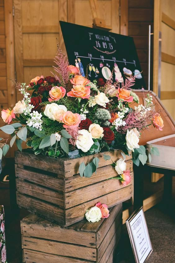 Decoración de bodas muy vintage. Un par de cajones de madera y una explosión de plantas y flores a la entrada de la recepción.