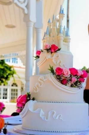 Were we inspired by the Disney castles when we were little and played in the sand? We think so. Romantic Disney castle cake with scroll piping and flowers perfect for a beach wedding.