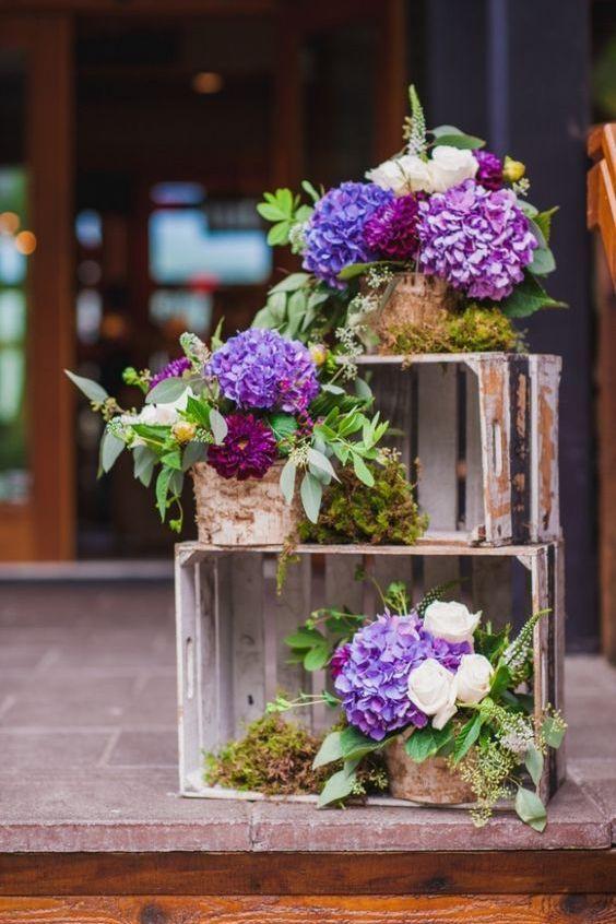 Ideas para la decoración con cajones de madera usados. Hortensias y ranúnculos en macetas rodeadas con musgo seco. Fotografía: Pebble and Pine Photography.
