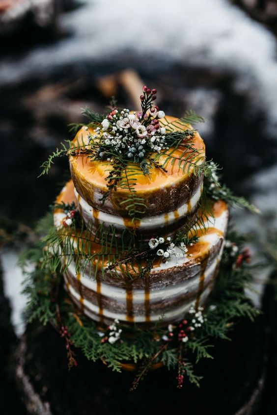 This alternative fall woodland wedding cake features winter inspired florals, a dripping cake and cozy romance!