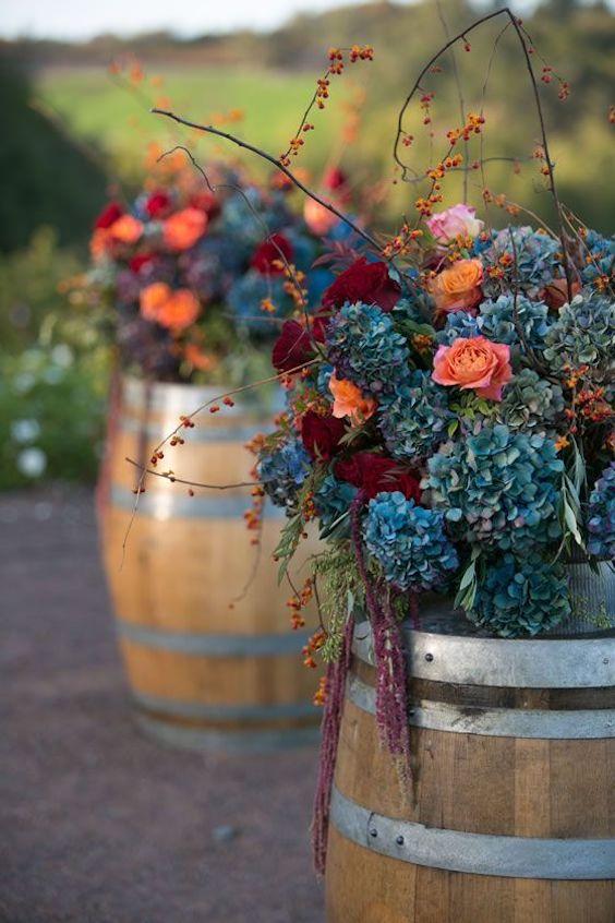 Estos arreglos florales con hortensias azules, ramas y rosas en coral lucen increíbles sobre estos barriles o en cajones de madera.