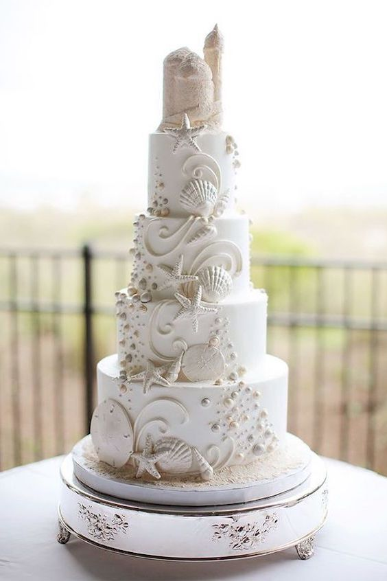 Incredible four tier beach wedding cake with seashells and edible sand castle cake topper.
