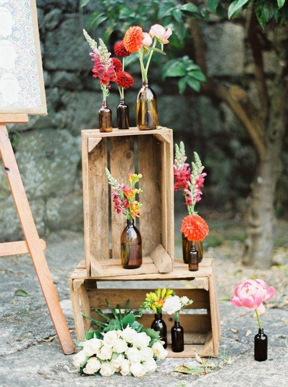 Ahorrar en una boda no implica que la misma no luzca original y divina. Decórala con cajones de madera usados, botellas y flores coloridas. Fotografía: Brancoprata.
