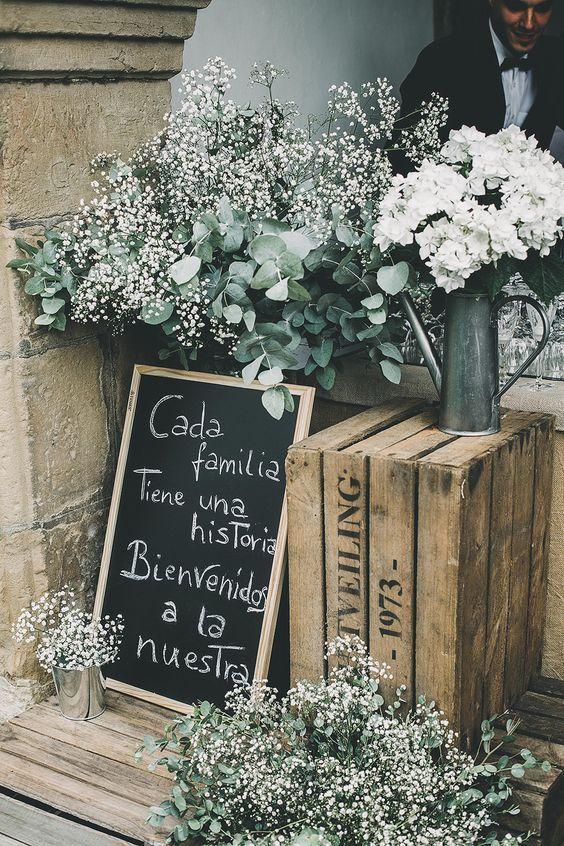 Una linda - y económica - forma de dar la bienvenida a tus invitados. Cajones de madera, eucaliptos y flores de relleno sumadas a una pizarra con una frase emotiva.