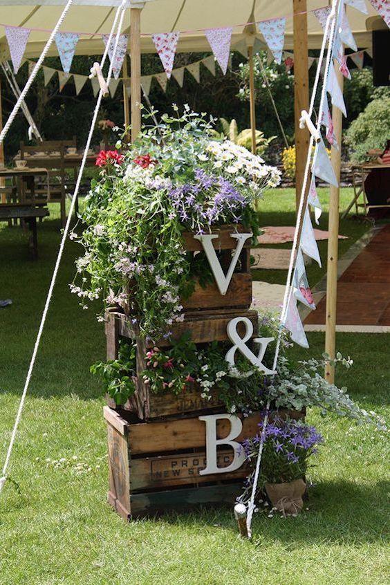 Una buena idea para cubrir los postes de las carpas para bodas y evitar que alguien se tope con ellos. Preciosos los banderines y las iniciales de los novios.